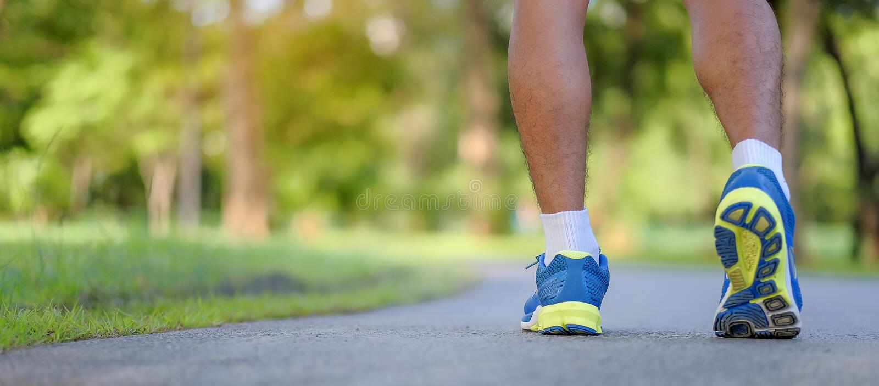 Giovani gambe dell'uomo di forma fisica che corrono nel parco all'aperto immagini stock libere da diritti