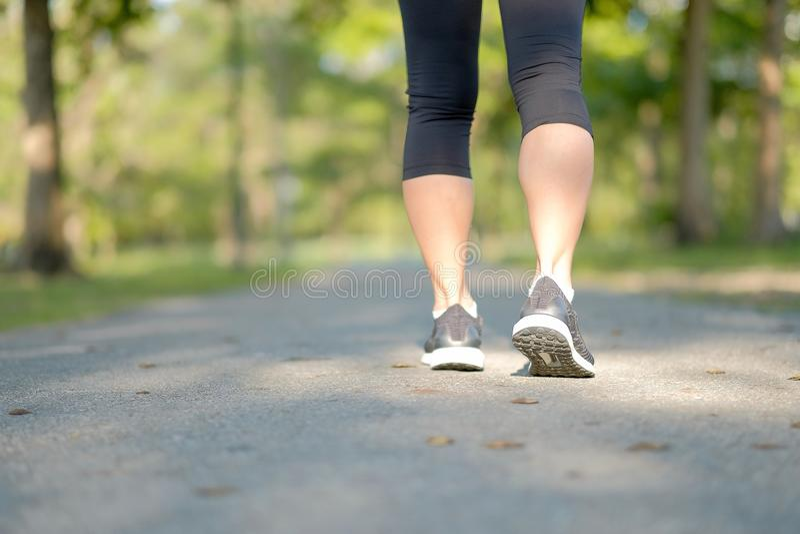 Giovani gambe della donna di forma fisica che camminano nel funzionamento all'aperto e femminile del parco del corridore sulla st fotografie stock