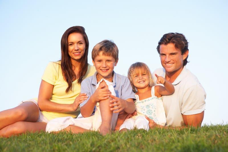 Giovani genitori, con i bambini, proponenti su un campo fotografie stock