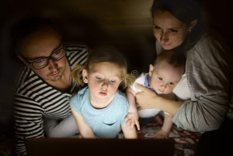 Giovani genitori con i piccoli bambini ed il computer portatile alla notte fotografia stock libera da diritti