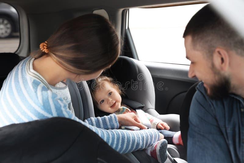 Giovani genitori con il bambino in automobile del sedile di sicurezza immagini stock