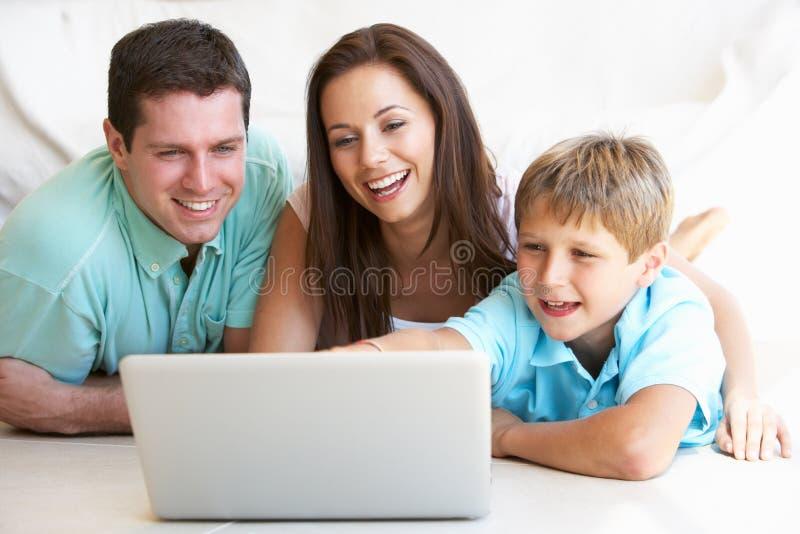 Giovani genitori, con il bambino, sul computer portatile fotografia stock libera da diritti