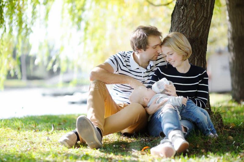 Giovani genitori con il loro bambino in parco soleggiato fotografia stock