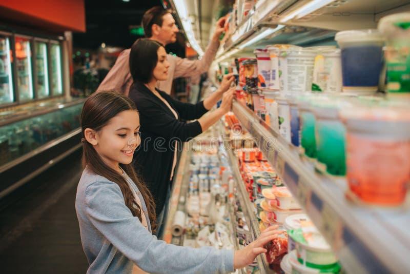 Giovani genitori e figlia in drogheria Stanno allo scaffale della latteria ed alla scelta Barattoli di tocco della ragazza e guar immagini stock