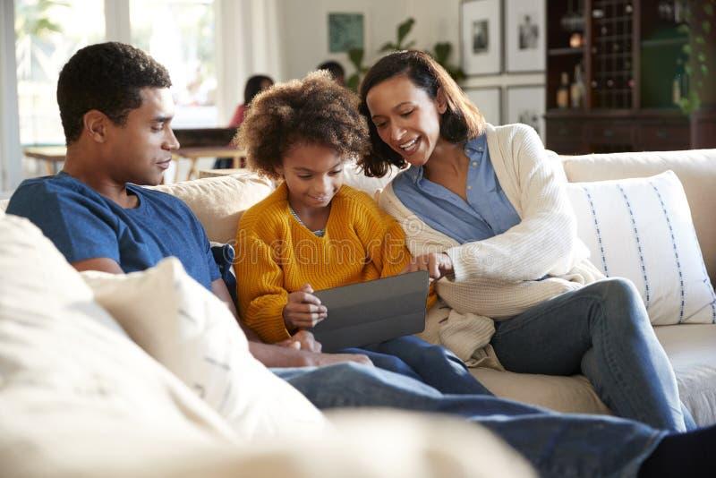 Giovani genitori e loro la figlia pre-teen che si siedono insieme su un sofà nel salone facendo uso di un computer della compress fotografia stock libera da diritti