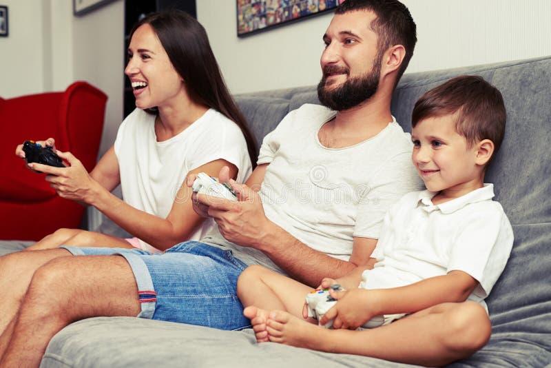 Giovani genitori e loro piccolo il figlio che giocano insieme videogioco fotografia stock