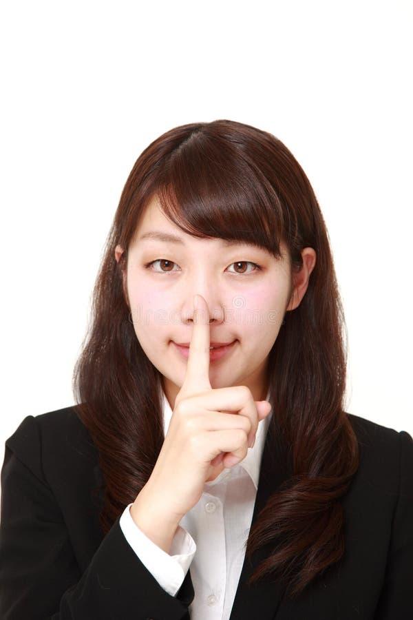 Giovani gesti giapponesi di silenzio del whith della donna di affari immagine stock libera da diritti