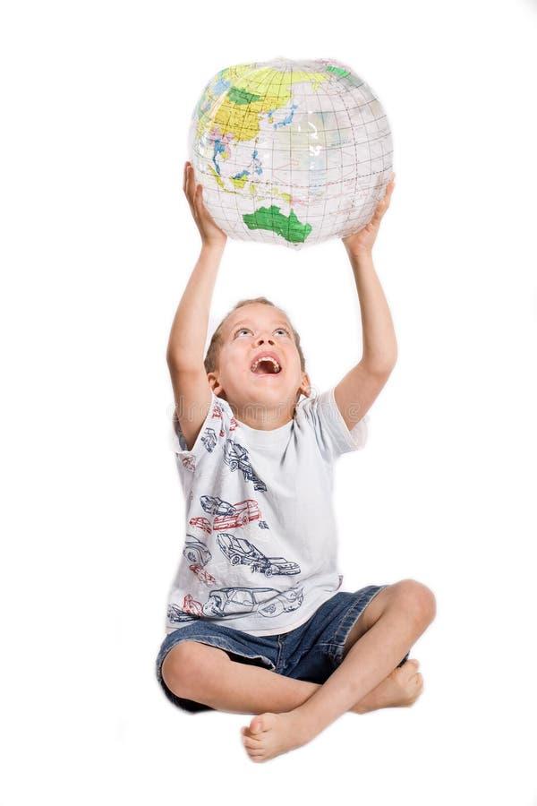 Giovani giochi del ragazzo con il globo fotografia stock libera da diritti