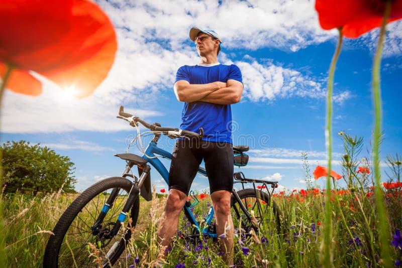 Giovani giri del ciclista sul campo del papavero immagini stock libere da diritti
