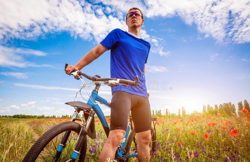 Giovani giri del ciclista sul campo del papavero fotografia stock