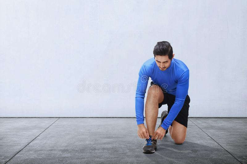 Giovani laccetti asiatici di sport del legame dell'uomo prima di correre fotografie stock