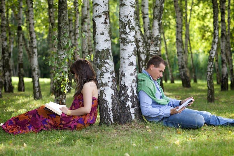 Giovani libri di lettura delle coppie in parco dal tronco di albero fotografie stock libere da diritti