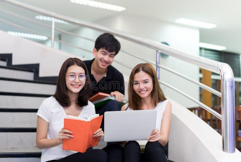 Giovani libro di lettura di Asian Group Teenager dello studente e computer portatile usando fotografie stock libere da diritti