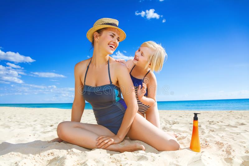Giovani madre e bambino sorridenti sulla spiaggia che applica SPF fotografia stock libera da diritti