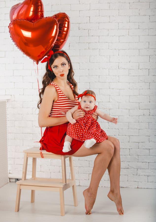 Giovani madre felice e figlia della famiglia che posano nello studio immagine stock