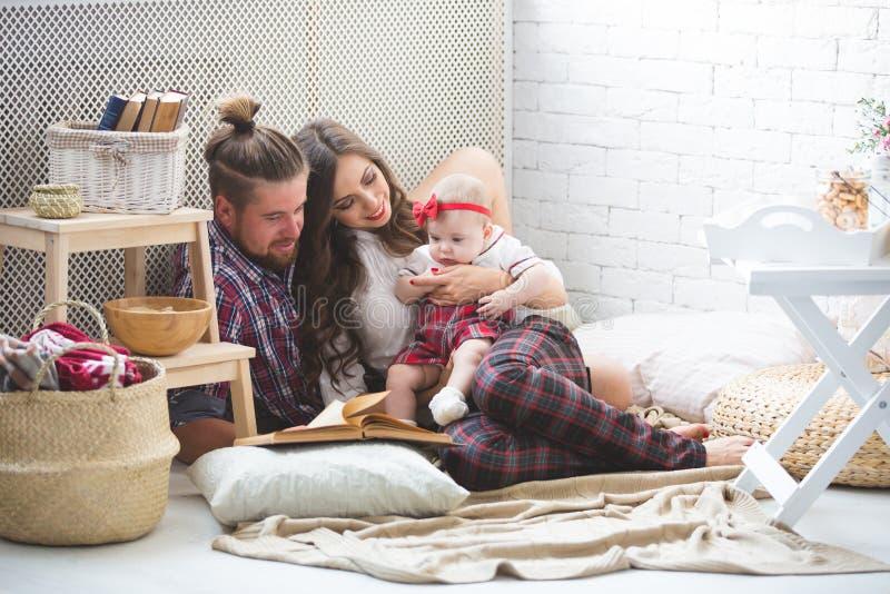 Giovani madre, padre felice e figlia della famiglia giocanti sul tappeto a casa fotografia stock libera da diritti