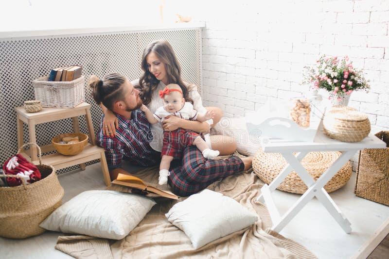 Giovani madre, padre felice e figlia della famiglia giocanti sul tappeto a casa immagine stock libera da diritti