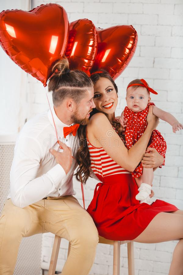 Giovani madre, padre felice e figlia della famiglia posanti nello studio immagini stock libere da diritti