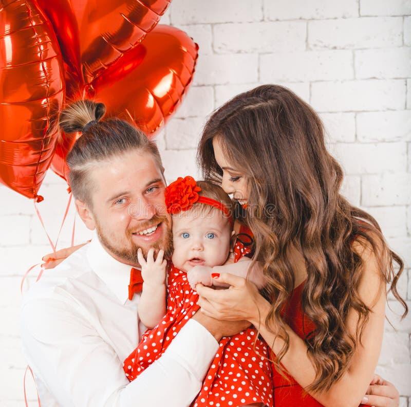 Giovani madre, padre felice e figlia della famiglia posanti nello studio fotografia stock