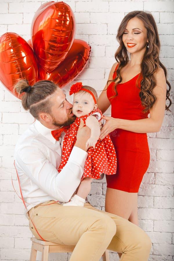 Giovani madre, padre felice e figlia della famiglia posanti nello studio immagine stock