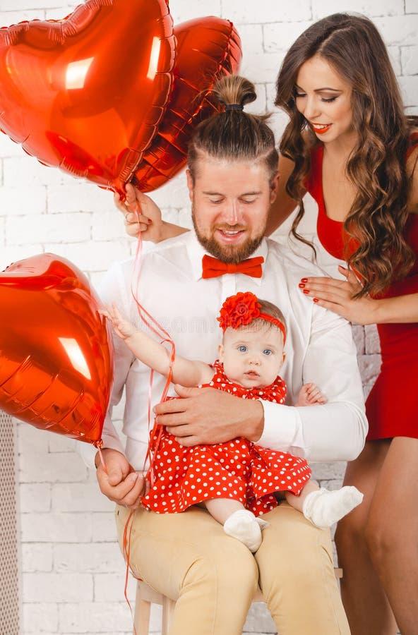 Giovani madre, padre felice e figlia della famiglia posanti nello studio fotografie stock