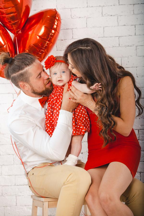 Giovani madre, padre felice e figlia della famiglia posanti nello studio fotografia stock libera da diritti
