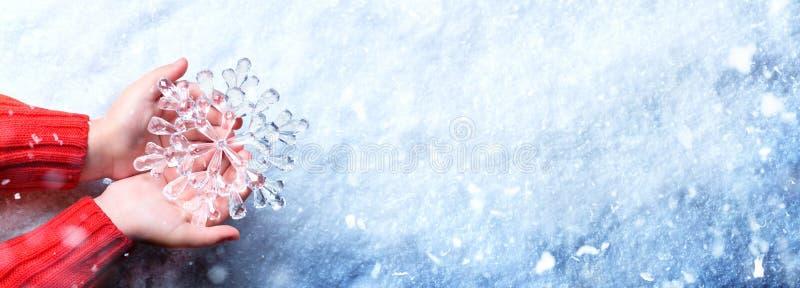 Giovani mani che tengono fiocco di neve - concetto di inverno fotografia stock