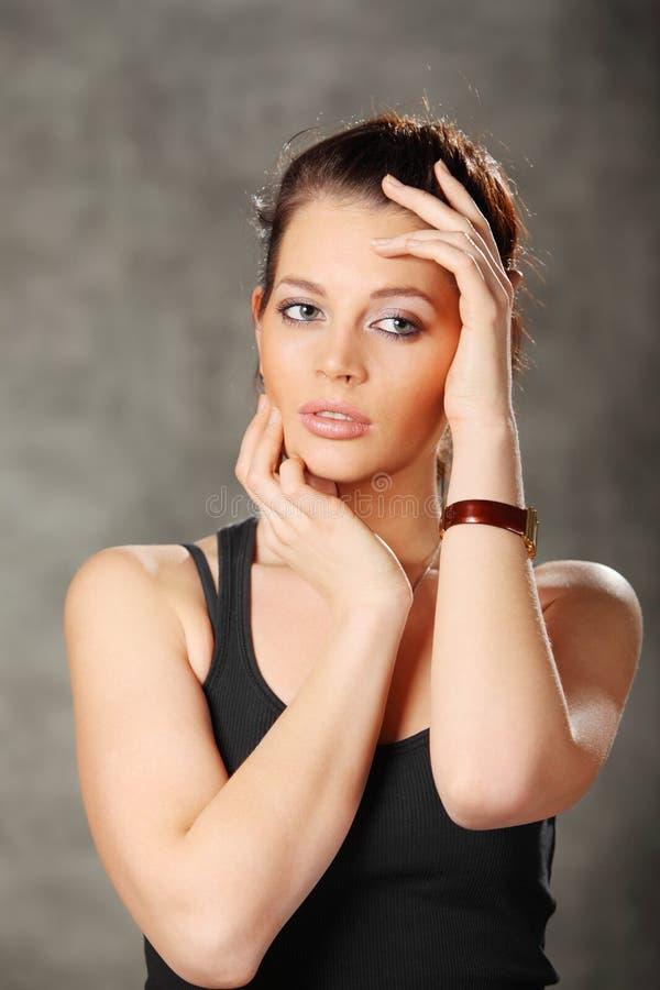 giovani mani della stretta della ragazza del brunette sul fronte immagini stock