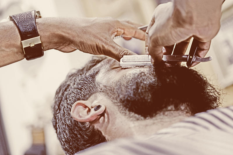 Giovani mani maschii che radono una barba fotografia stock