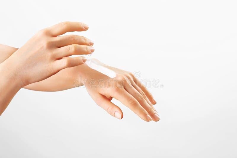 Giovani mani sane Idratante d'applicazione femminile alle sue mani Cura di pelle fotografie stock