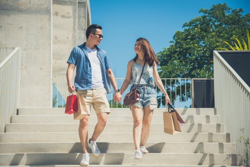 Giovani mano e sorriso della tenuta delle coppie mentre camminando fotografie stock