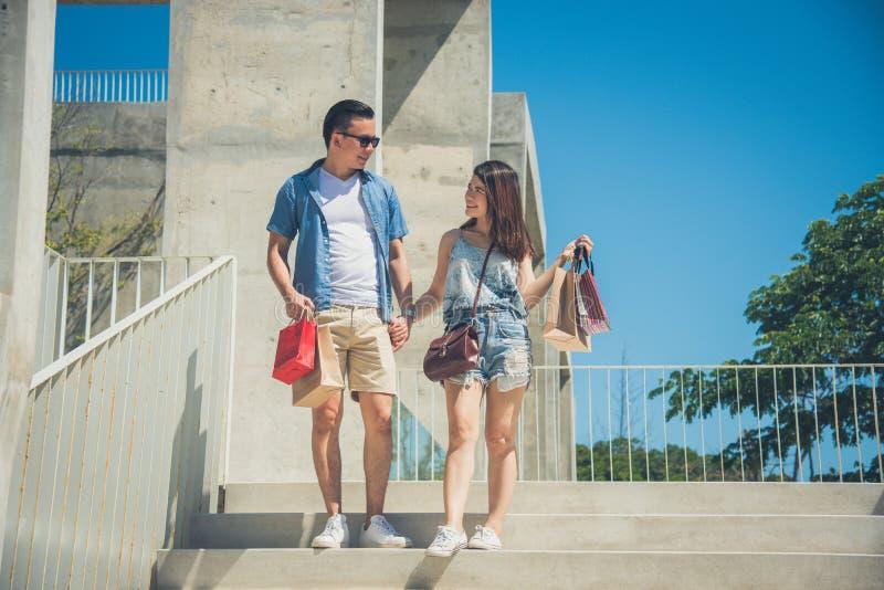 Giovani mano e sorriso della tenuta delle coppie mentre camminando fotografia stock libera da diritti