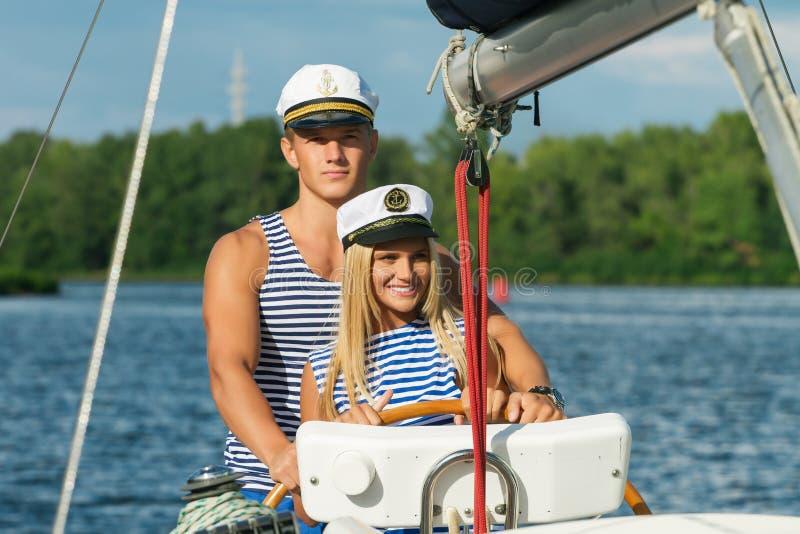 Giovani marinai dell'uomo e della donna delle coppie al timone di immagini stock