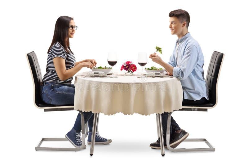 Giovani maschio e femminile mangiando un'insalata in un ristorante immagine stock libera da diritti