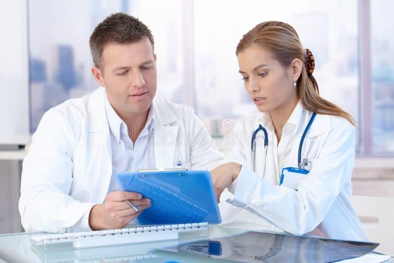 Giovani medici che discutono diagnosi nell'ufficio fotografie stock