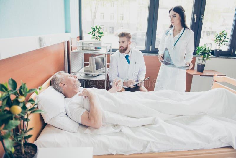 Giovani medico ed infermiere stanno visitando il paziente invecchiato alla m. luminosa immagine stock libera da diritti