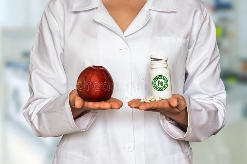 Giovani mela della tenuta di medico e bottiglia delle pillole con il Fe del ferro, COM fotografia stock libera da diritti