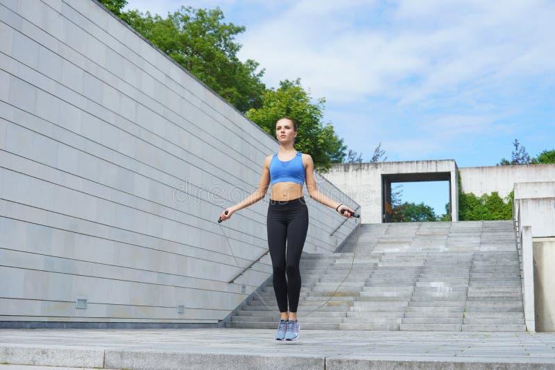 Giovani, misura e donna sportiva saltanti con un salto della corda Forma fisica, sport, pareggiare urbano e concetto sano di stil fotografie stock libere da diritti