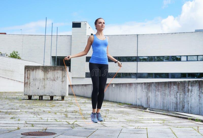 Giovani, misura e ragazza sportiva saltanti con un salto della corda immagine stock libera da diritti