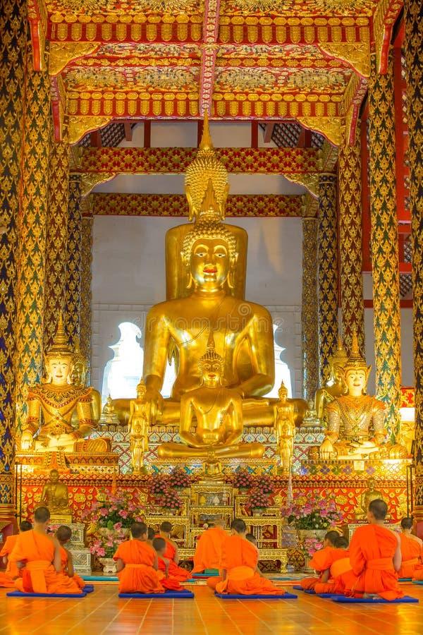 Giovani monaci buddisti che pregano davanti all'immagine di Buddha immagine stock