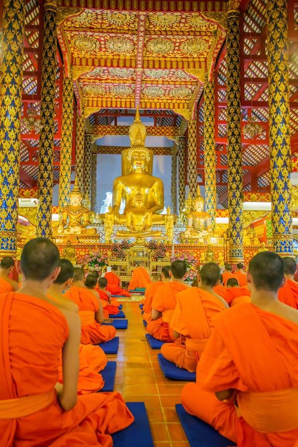 Giovani monaci buddisti che pregano in tempio di Wat Suan Dok fotografia stock