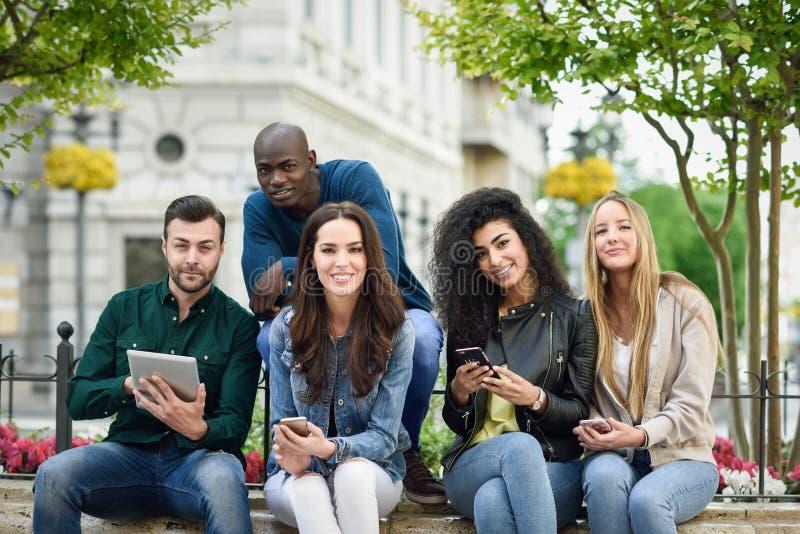 giovani Multi-etnici che per mezzo dei computer della compressa e dello smartphone immagini stock libere da diritti