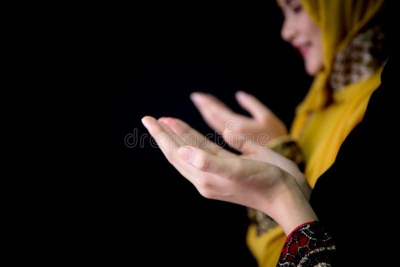 giovani musulmani religiosi due donne che pregano su fondo nero immagini stock libere da diritti