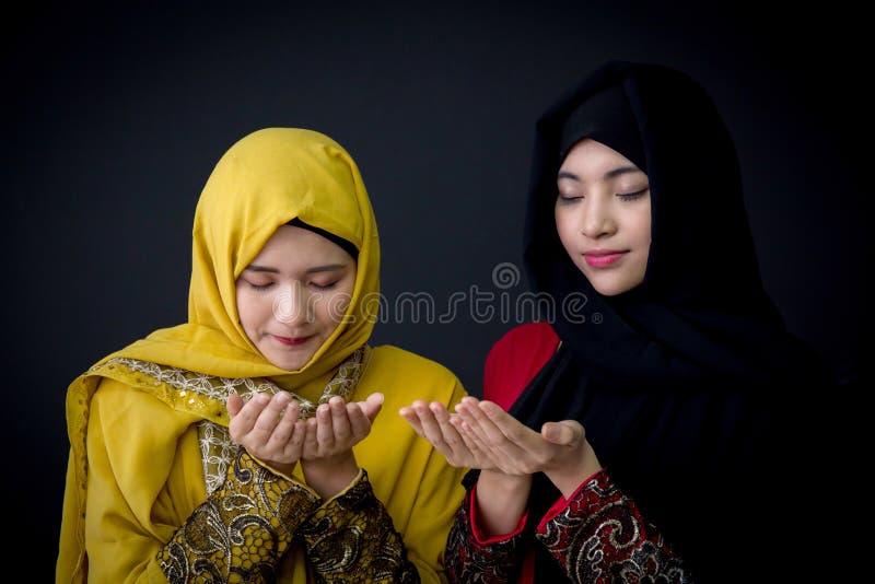 giovani musulmani religiosi due donne che pregano su fondo nero fotografia stock