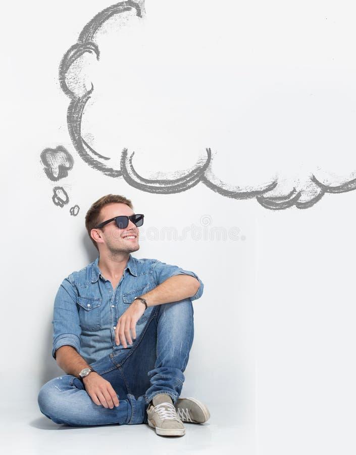 Giovani occhiali da sole caucasici di usura di uomo mentre sedendosi sul pavimento t fotografia stock libera da diritti