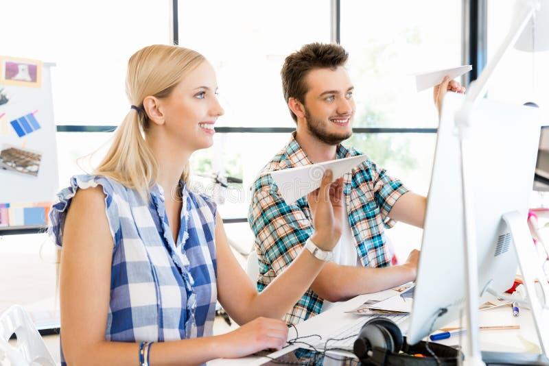 Giovani operai che giocano con l'aeroplano di carta in ufficio immagini stock libere da diritti