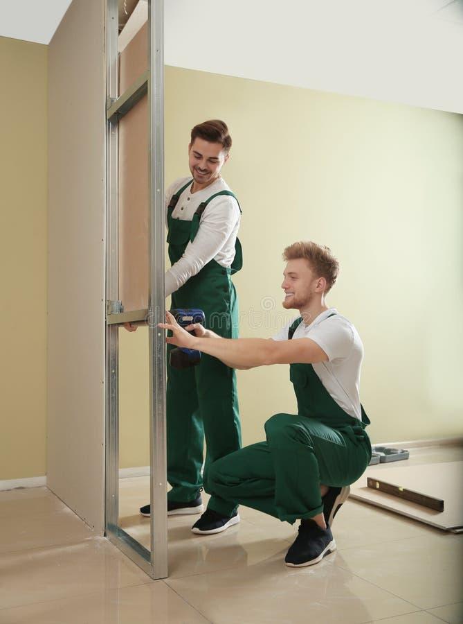 Giovani operai che installano muro a secco Servizio di riparazione domestico fotografie stock libere da diritti
