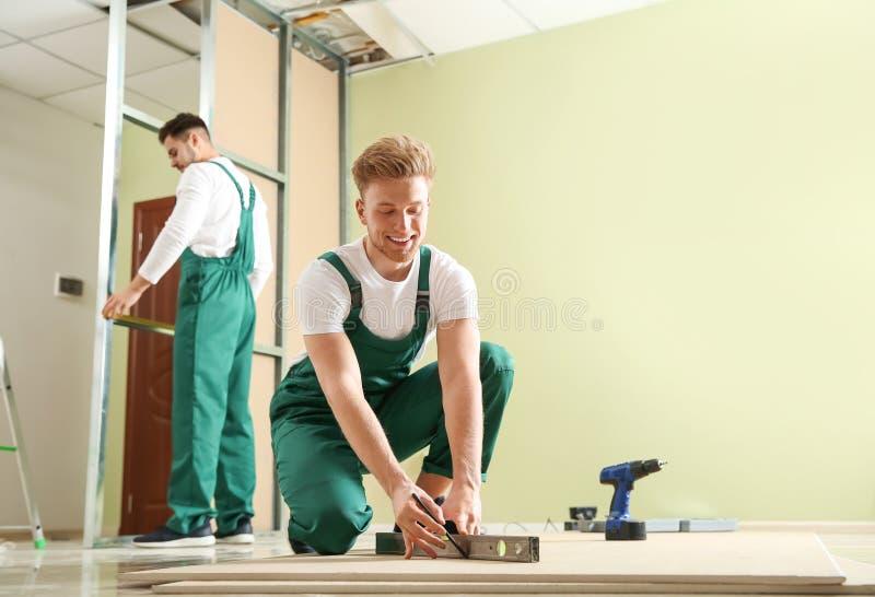 Giovani operai che installano muro a secco Servizio di riparazione domestico fotografie stock