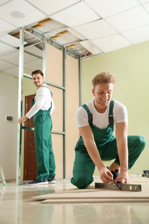 Giovani operai che installano muro a secco Servizio di riparazione domestico fotografia stock libera da diritti