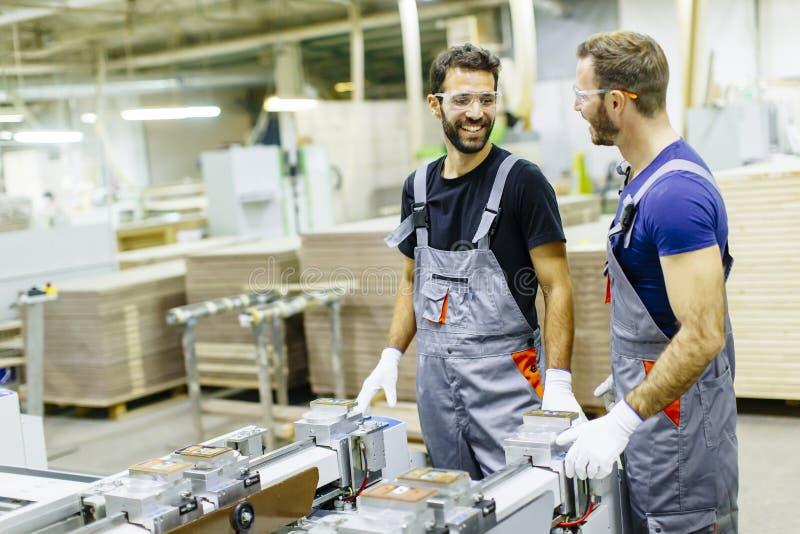 Giovani operai che lavorano nella fabbrica della mobilia immagini stock libere da diritti